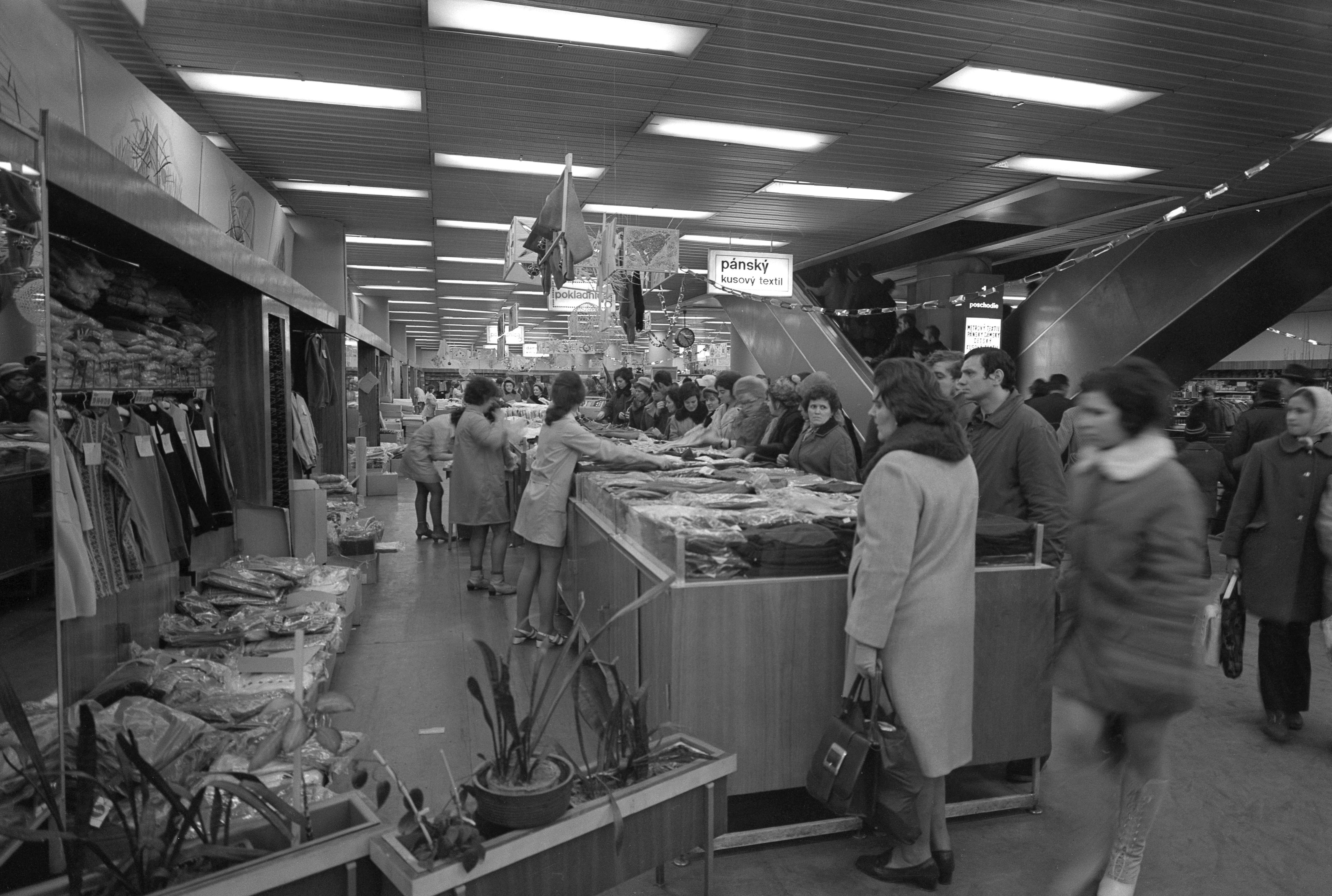 Na archívnej snímke z 20. decembra 1973 kupujúci si prehliadajú textilné výrobky počas predvianočných nákupov v novom obchodnom dome Prior v Košiciach.