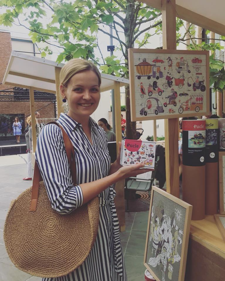 Jednou z ilustrátoriek je aj Simona Čechová, ktorá na markete v Trnave drží v rukách svoje dizajnové Pucle.