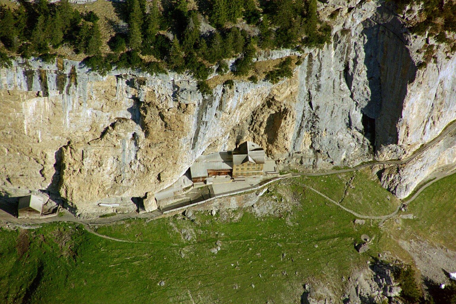 Letecký pohľad na alpský útes, pod ktorým je učupená horská chata Aescher.